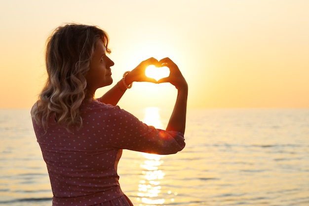 Young woman in pink dress with heart-shaped fingers wrapping her fingers around the sun at sunset