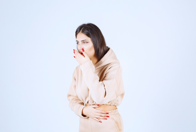 Young woman in a pink hoodie caughing and has sore throat