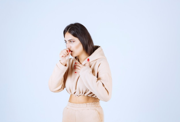Young woman in a pink hoodie caughing and has sore throat Free Photo