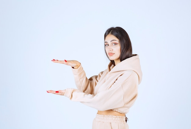 Young woman in a pink hoodie demonstrating the estimated measures of an object