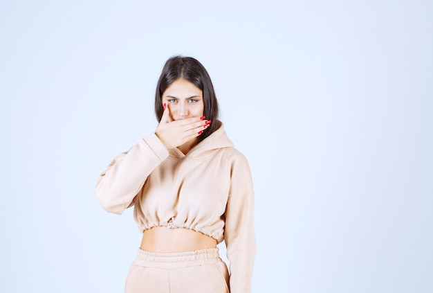 Young woman in a pink hoodie frightened and scared