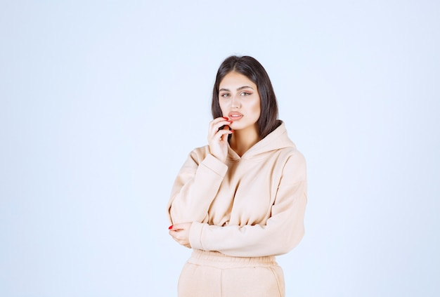 Young woman in a pink hoodie looks confused and thoughtful