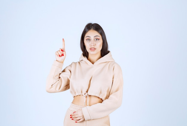 Young woman in a pink hoodie pointing upside