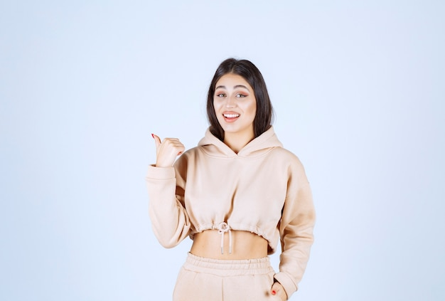 Young woman in a pink hoodie pointing behind