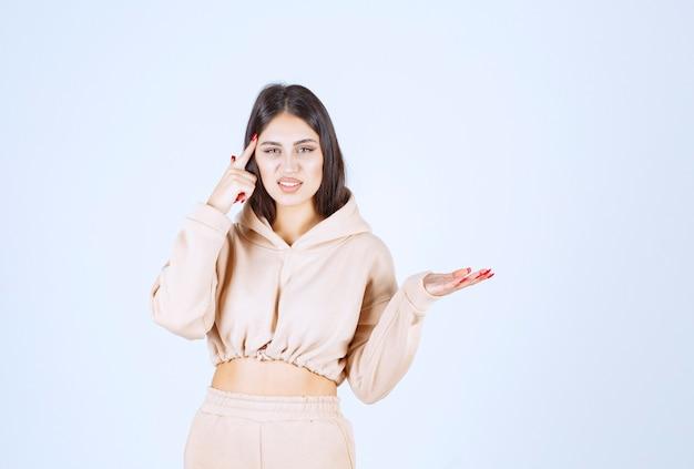 Giovane donna in una felpa con cappuccio rosa che presenta qualcosa nella sua mano aperta