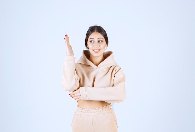 Young woman in a pink hoodie raising her hand