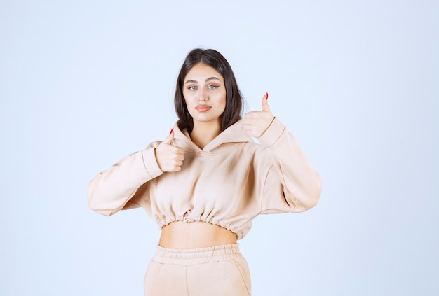 Young woman in a pink hoodie showing good hand sign