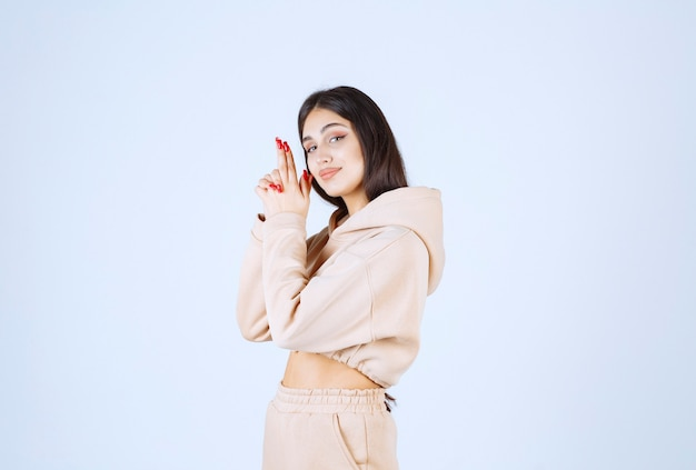 Young woman in a pink hoodie showing gun sign