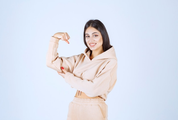 Giovane donna in una felpa con cappuccio rosa che mostra i suoi muscoli