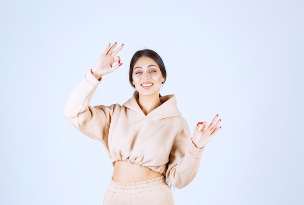 Young woman in a pink hoodie showing satisfaction hand sign