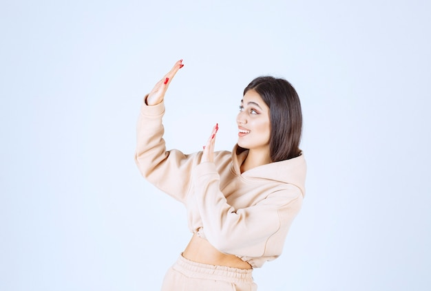 Young woman in a pink hoodie stopping someone