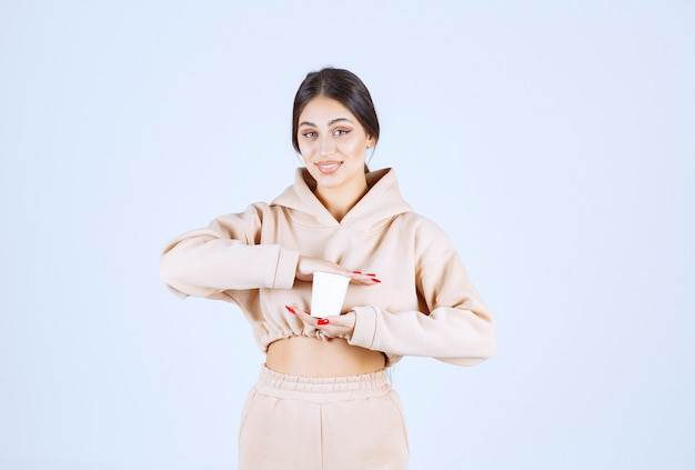 Young woman in pink pajamas holding a cup of drink