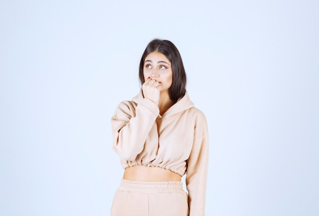 Young woman in pink pajamas looks surprized and terrified