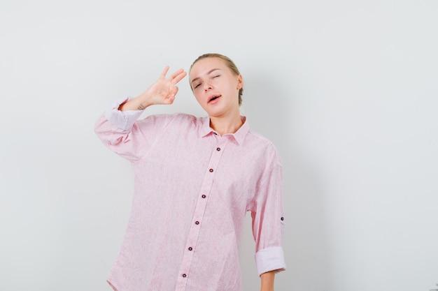 Giovane donna in camicia rosa che mostra segno giusto e occhi ammiccanti