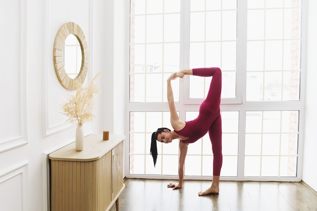 Young woman in pink sportswear practicing yoga at home near the window performing a variation of the crescent moon pose ardha chandrasana