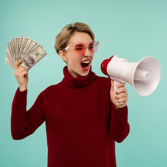Young woman in pink sunglasses with money yelling to loudspeaker