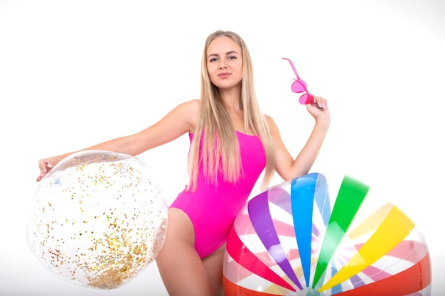 A young woman in a pink swimsuit holds a colored inflatable balls