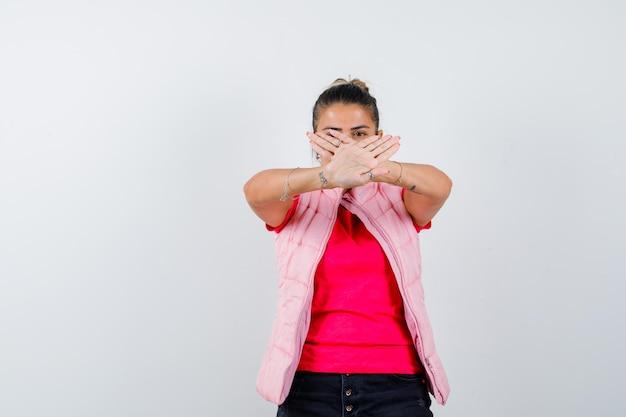Giovane donna in maglietta e giacca rosa che mostra restrizione o gesto x e sembra seria