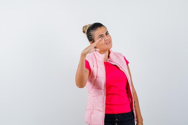 Giovane donna in maglietta rosa e giacca che allunga la mano mentre mostra la scala e sembra bellissima scale