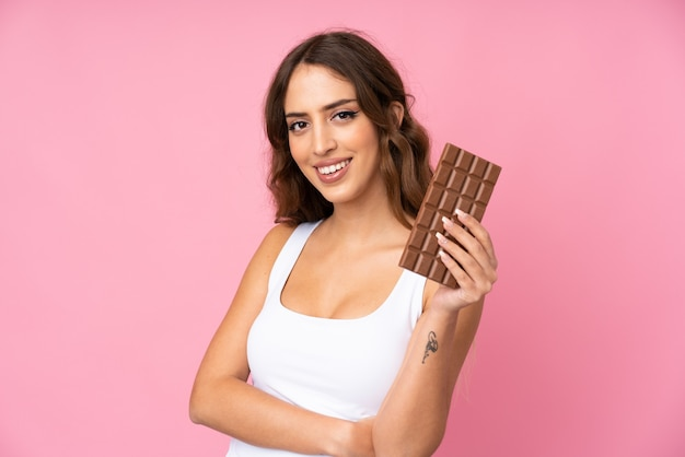 Young woman   pink  taking a chocolate tablet and happy