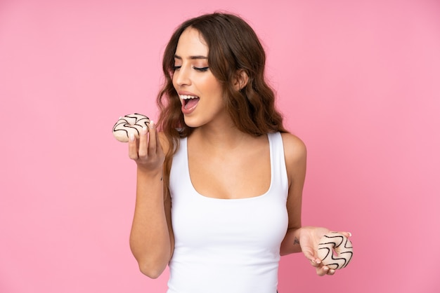 Young woman over pink wall eating a donut