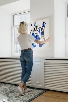Молодая женщина ставит абстрактные краски на стену