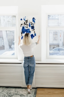 Young woman placing abstract paint on the wall