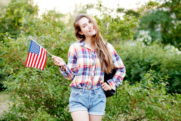 Young woman in plaid shirt and shorts holding american flag