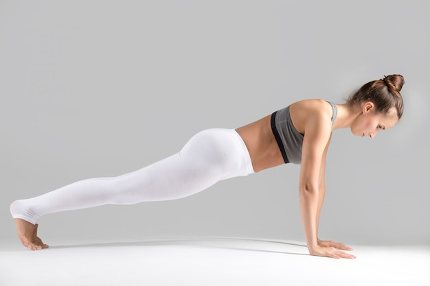 Young woman in plank pose, grey studio background