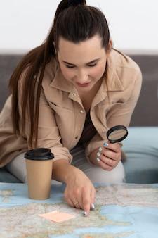 地図で旅行を計画している若い女性
