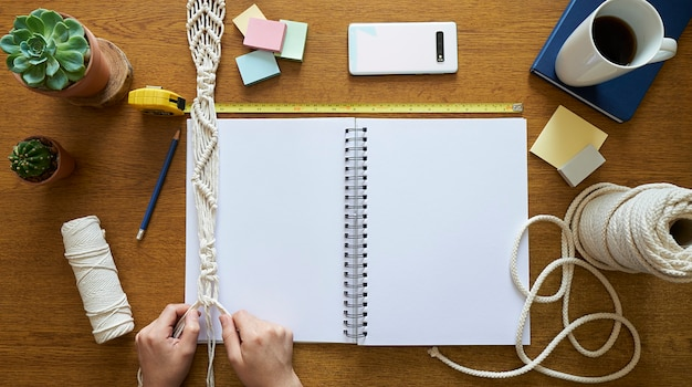 Young woman planning and working on a macrame handmade decor on a wooden desk Premium Photo