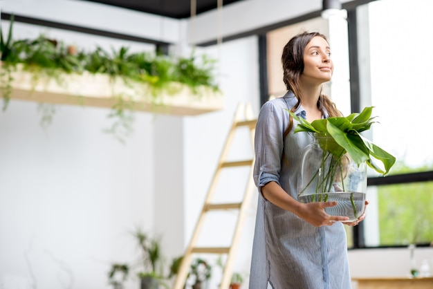 部屋に大きな植物と緑の立っている家を植える若い女性