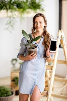 Молодая женщина сажает дом с зеленью, стоя с телефоном и цветочным горшком на лестнице