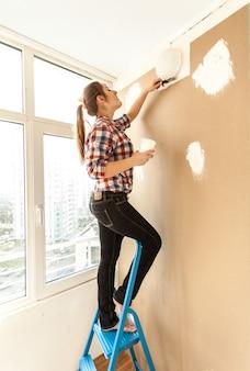 Молодая женщина оштукатуривает стену на высокой лестнице