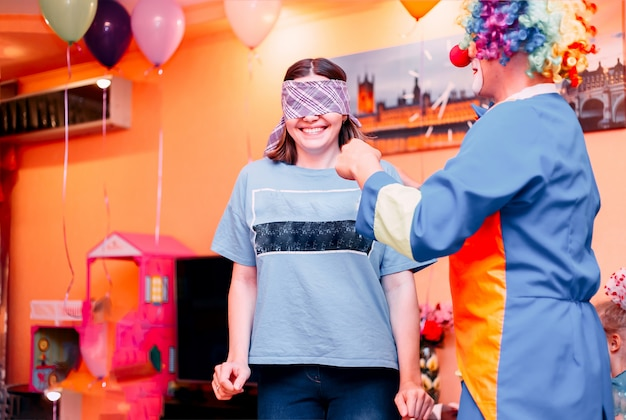 Young woman play blind man's buff with clown