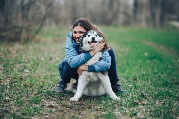 Young woman play with husky dog for a walk in spring forest. laughing having fun, happy with pet