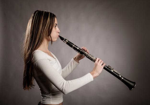 Молодая женщина играет на кларнете на сером