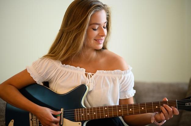 Молодая женщина играет на гитаре, сидя на диване у себя дома