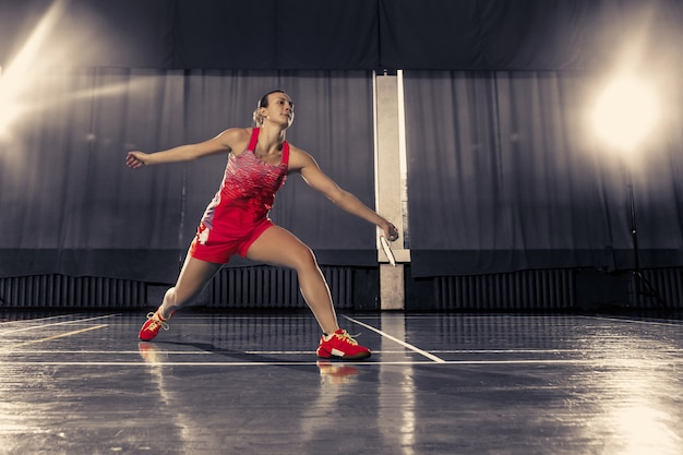 Young woman playing badminton over gym space
