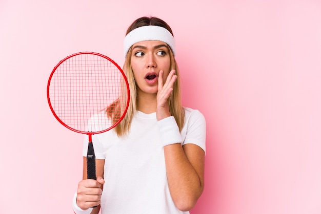Young woman playing badminton isolated is saying a secret hot braking news and looking aside