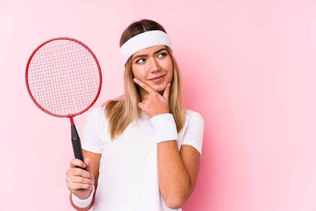Young woman playing badminton isolated looking sideways with doubtful and skeptical expression.