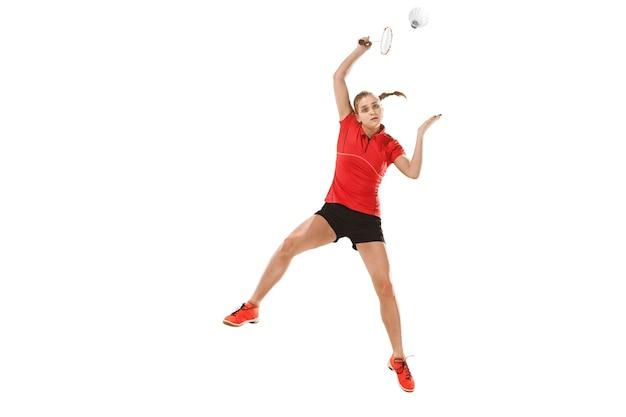 Молодая женщина играет в бадминтон на фоне белой студии. подходит спортсменка, изолированные на белом. бадминтонист в действии, движении, движении. концепция атаки и защиты