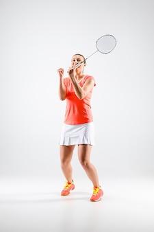 Молодая женщина играет в бадминтон на белой стене