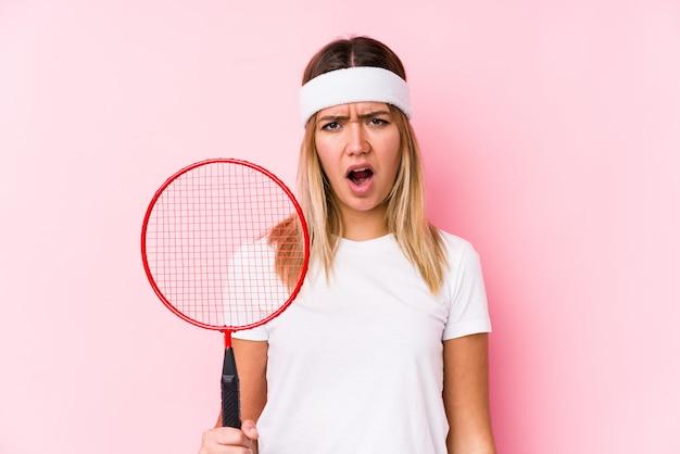 Молодая женщина играет в бадминтон, кричать очень злой и агрессивный.