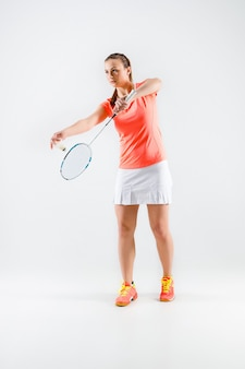 Young woman playing badminton over white wall