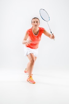 Young woman playing badminton on white