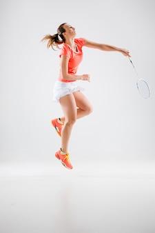 Giovane donna che gioca a badminton sopra bianco