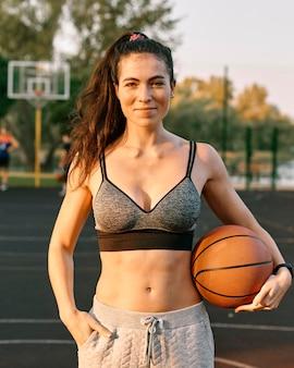 Молодая женщина играет в баскетбол в одиночестве на улице