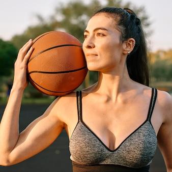 Молодая женщина играет в баскетбол в одиночестве