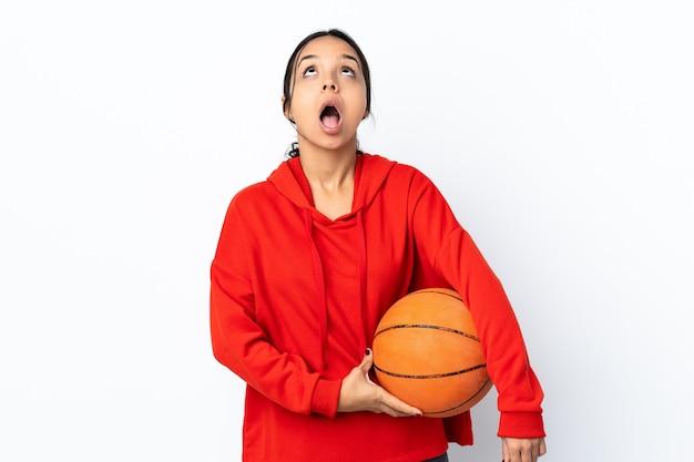 バスケットボールをしている若い女性は、見上げると驚いた表情で孤立した